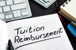 Tuition reimbursement written on a page of notepad.