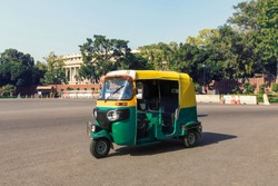 Tuk tuk - traditional indian moto rickshaw taxi on one of the street of New Delhi. yellow green tricycle stands on the square against the background of the presidential Palace.