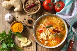 Tukpa soup of Indian cuisine. Hot noodle soup with chicken, ginger, cilantro and spices on a deyven wooden table. Top view flat lay background.