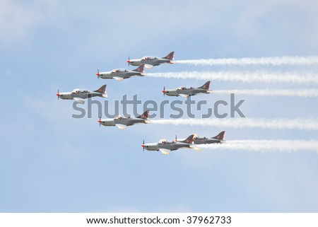 TUKUMS - AUGUST 1: Group of flying aerobatic sport airplanes. Formation with smoke trails. Airshow event, August 1, 2009 in Tukums airfield, Latvia.