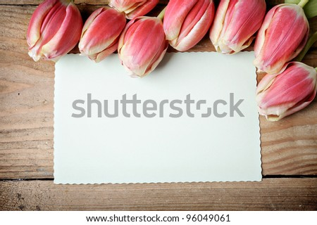 Tulips and blank card on old wooden boards