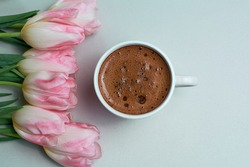 Tulips and cup of coffee on white background. Concept woman's or mother's day top view