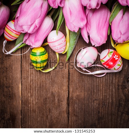 Tulips and eggs border over wooden backdrop. Easter decorations.