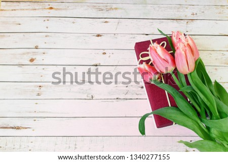 Tulips and gift box on a white wooden background. Celebration. Present. March 8, Mother's Day, Valentine's Day. copy space. Copy space. Flat lay, top view.
