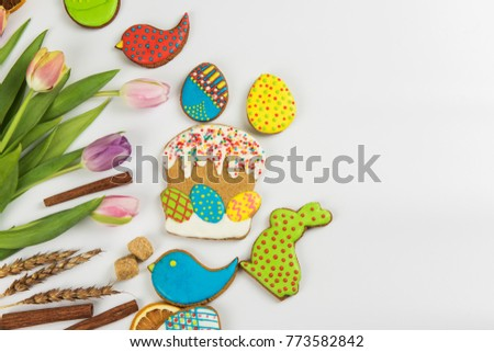 Tulips and gingerbread cookies on white background for Easter. #773582842