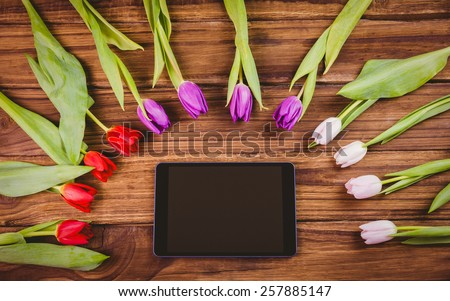 Tulips forming frame around tablet on wooden table