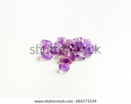 Tumbled Amethyst stones close up on table for crystal therapy treatments and reiki #686571034