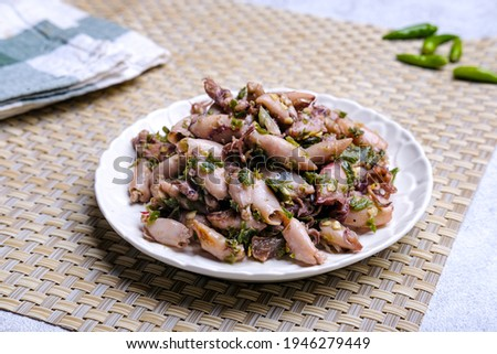 Tumis cumi asin cabe ijo or stir-fried salted squid with green chili. Indonesian traditional dish. Blurred background and selective focus.  Stock fotó ©