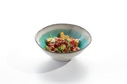 Tuna and cucumber salad bowl. Blue salad bowl isolated on white background. Salad garnished with micro greens and sesame, chopped tuna, sliced cucumber and parsley green leaf. Raw tuna spicy sauce