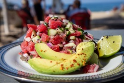 Tuna Ceviche Tostada served with avocado and lime on the beach in Mexico