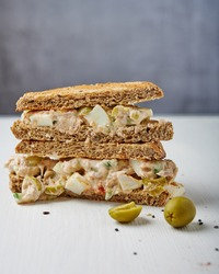 Tuna egg salad sandwich with green olives and black salt on the side on white wooden table against grey background