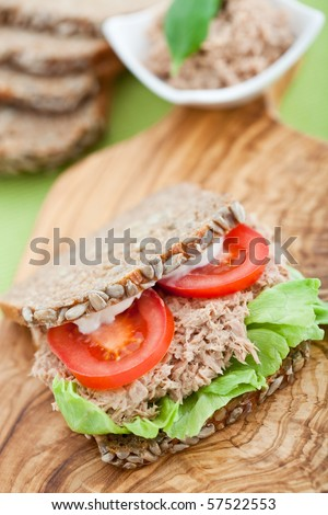 Tuna fish sandwich with tomatoes, lettuce and mayonnaise on a wooden board. Shallow DOF