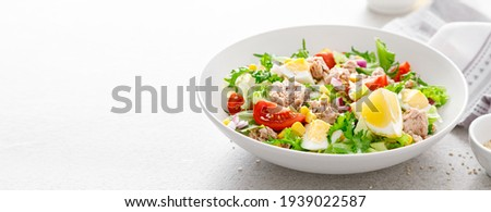Tuna salad with boiled egg, tomato, lettuce, corn and red onion. Healthy and detox food concept. Ketogenic diet. Fresh vegetable salad bowl on white background. Banner