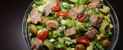Tuna salad with lettuce, olives, spring onions, cherry tomato, corn and avocado. Canned Tuna fish salad. Food background. Close up. Panoramic image, hi-res banner. Full depth of field.
