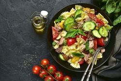 Tuna salad with pasta and vegetables in a black bowl on a dark slate,stone or concrete background.Top view.