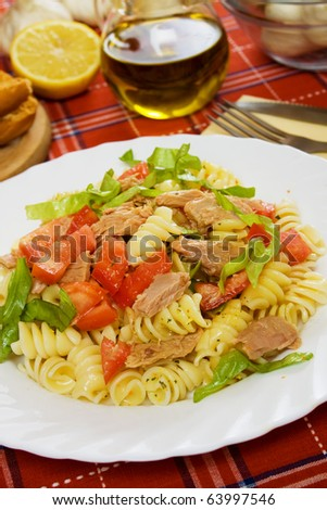 Tuna salad with pasta, lettuce and tomato on white plate