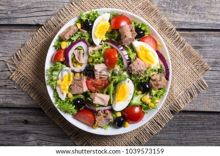 Tuna salad with tomatoes , olives , eggs and onion . #1039573159