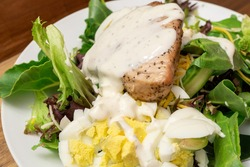 Tuna Steak on a bed of mixed greens with red leaf lettuce and spinach, cheese, and hard boiled eggs