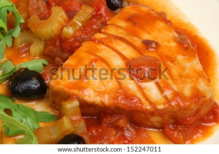 Tuna steak poached in tomato sauce.