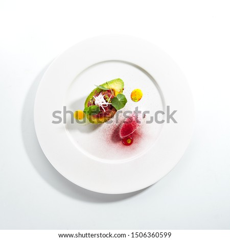 Tuna tartar made from raw fish served in avocado with lime ice cream on white restaurant plate isolated. Exquisite serving yellowfin sashimi tatar in alligator pear with gourmet dessert topview