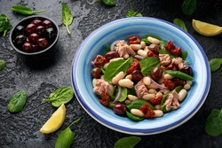 Tuna, white bean salad with olive, red onion, spinach and dried tomato. Healthy food.