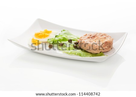 Tuna with lettuce salad and hard boiled egg on white tray isolated on white background. Culinary seafood eating.