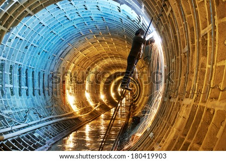 Tuneller welder working with electrode at arc welding in underground subway metro construction site stock photo