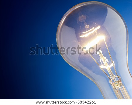 tungsten lightbulb on blue background. Horizontal shape, copy space