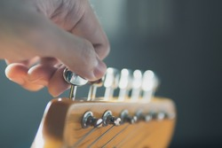 Tuning guitar string by adjusting tuning machines