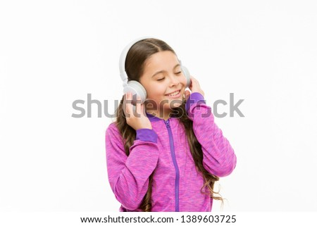 Tuning into a wave of real sound. Cute kid listening to sound track isolated on white. Active child enjoy electronic sound playing in earphones. Athletic little girl relaxing with melodious sound.