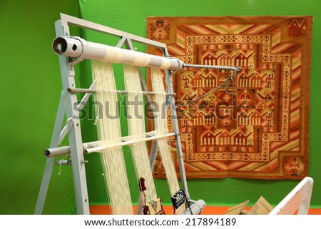 Tunis, Tunisia - December 15, 2013: National Exhibition of Handmade work in Tunis. Metal loom for weaving carpets with the Margoum carpet background