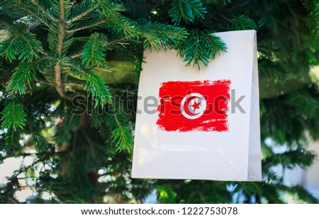 Tunisia flag printed on a Christmas shopping bag. Close up of a shopping bag as a decoration on a Xmas tree on a street. New Year or Christmas shopping, local market sale and deals concept.