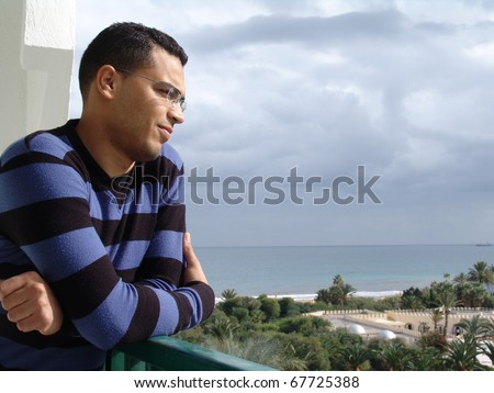 Tunisian man standing on balcony watching tunisian beach resort