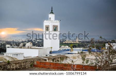 Tunisian Mosque (Rooftop) and Tower in Sidi Bou Said at sunset, with the capital city in the distance - Tunis, Tunisia [Africa]   #1006799134