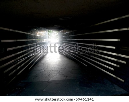 Tunnel passageway towards bright light - stock photo