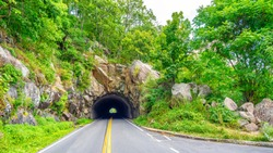 Tunnel through rocks along the skyline drive national park. The skyline drive is 105 miles long and runs along the blue ridge parkway in the appalachian mountains.