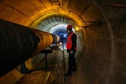 Tunnel worker examines pipeline in underground tunnel
