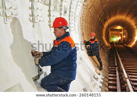 Tunneller worker installing fixture in underground subway metro construction site stock photo