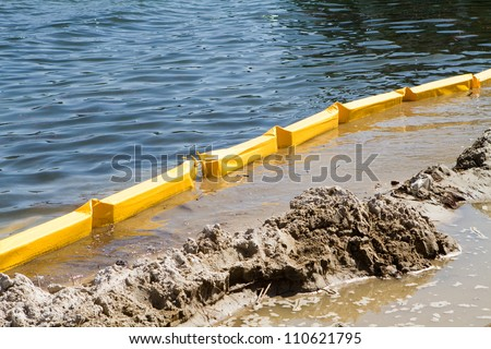 Turbidity curtain used at this construction site along the inter-coastal waterway to trap silt and sediment and keep it from polluting the water during excavations. - stock photo