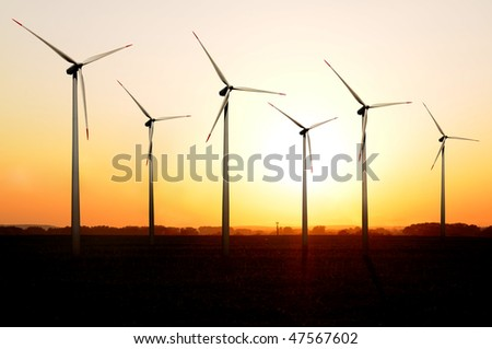 Turbines of a wind farm at sunset.