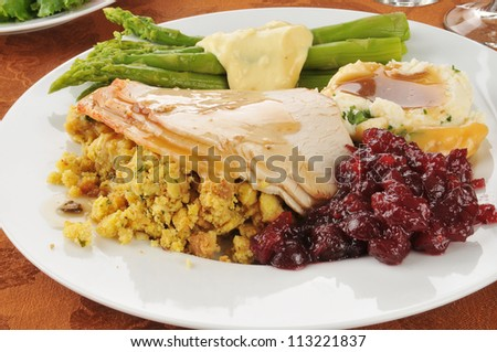 Turkey and dressing with asparagus and cranberry sauce