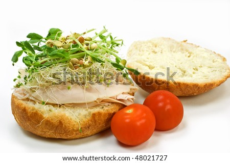 Turkey and sprouts on kaiser bun with cherry tomatoes isolated on white background