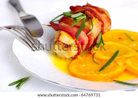 Turkey breast rolls in bacon with orange sauce - stock photo