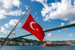 Turkey flag waving in wind over the Bosphorus strait in Istanbul, Turkey