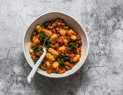Turkey, kale cabbage, tomato sauce hash and potato gnocchi -  delicious mediterranean style lunch on a gray background, top view