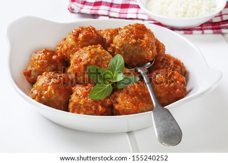 Turkey meatballs in tomato sauce with a spoon.