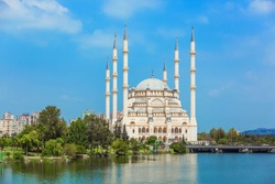 Turkey's largest Sabanci Central Mosque in Adana by Seyhan river among bright foliage of trees and against the blue sky