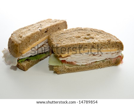 Turkey Sandwich with cheese, lettuce, tomato on brown bread