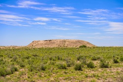 Turkic mound in the steppe. Burial ground of ancient Türks. Historical places. Burial place of the Turks near the ancient settlement. Barrow in the Kazakh steppe. Clouds in the blue sky
