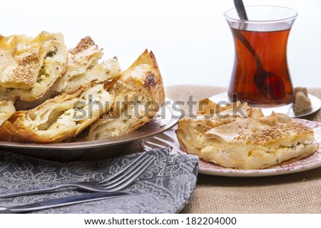 Turkish borek served at a party with cut portions heaped on a plate showing the crispy flaky texture of the yufka,or phyllo, pastry
